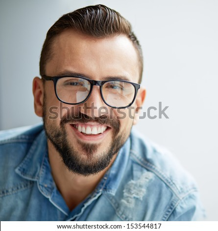Happy man in denim shirt and eyeglasses looking at camera with toothy smile #153544817