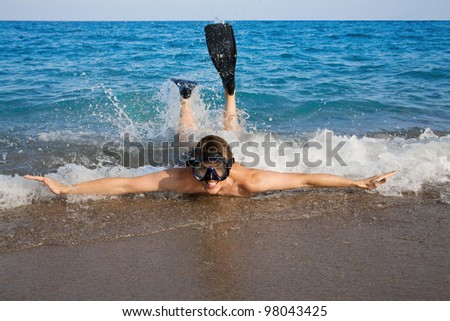 Happy man in goggles and flippers doing splashing in the red sea