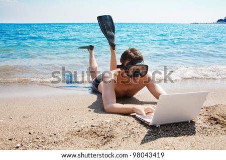 Happy man in goggles and flippers typing on the laptop at the beach