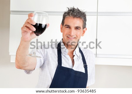 Happy man in kitchen drinking red wine and cheering