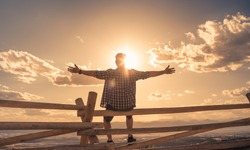 Happy man in nature sunset setting with arms up feeling free and energized.