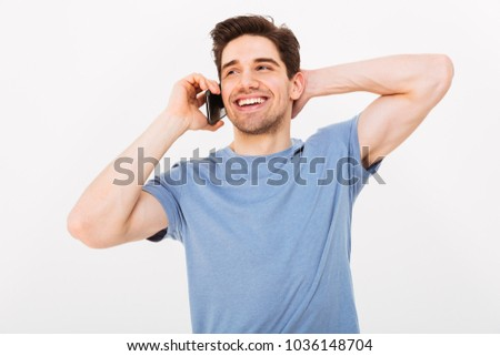 Happy man in t-shirt taking by smartphone while holding his head and looking away over grey background
