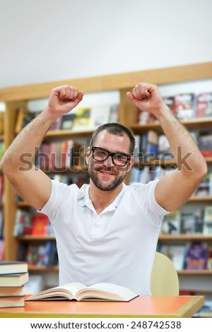 Happy man in the library works and studies
