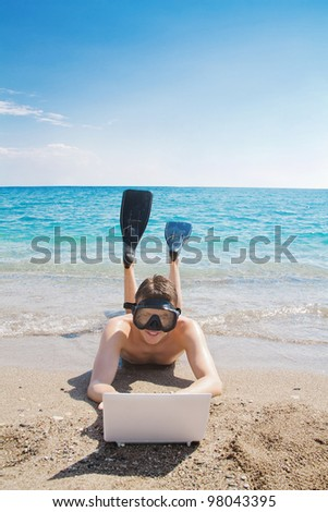 Happy man in underwater mask and flippers looking at the laptop at the beach