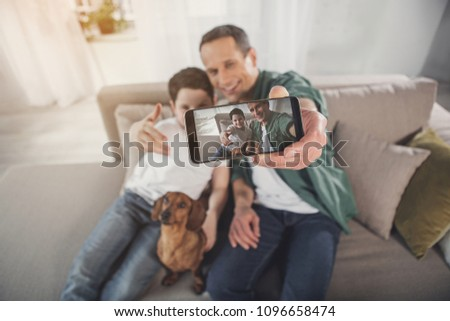 Happy man is making selfie with his son and dog on smartphone. They are embracing and smiling while sitting on sofa. Focus on gadget screen