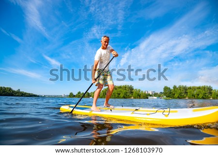 Happy man is paddling on a SUP board on a large river at sunny day. Stand up paddle boarding - awesome active recreation in nature.  Wide angle.