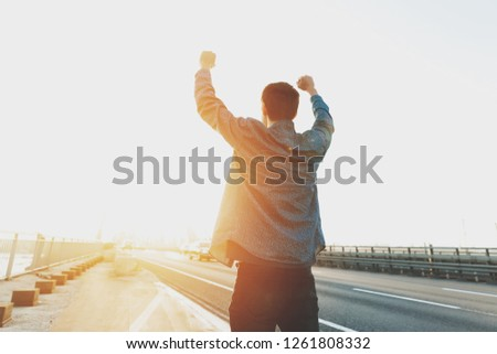 Happy man is standing with his arms raised up. Happy man jumping for joy with his hands up. Happy young man at sunrise on a busy bridge cars. The concept of a free and joyful person