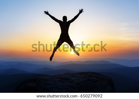 Happy man jumping for joy on the peak of the mountain, cliff at sunset. Success, winner, happiness #650279092
