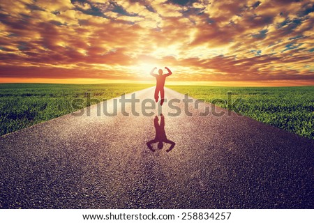 Happy man jumping on long straight road, way towards sunset sun. Travel, happiness, win, healthy lifestyle concepts.