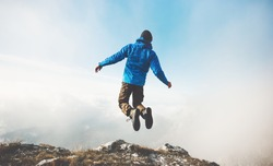 Happy Man jumping on mountains cliff to clouds sky Lifestyle Travel emotional success concept adventure active vacations outdoor