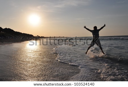 Happy man jumping over sea. Sand beach at sunset. Cuba vacation.