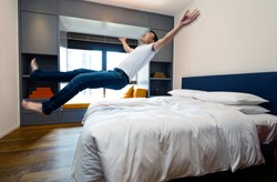 Happy man jumping to the bed.