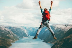 Happy Man jumping Travel Lifestyle adventure concept active summer vacations with backpack outdoor in Norway success and fun emotions above Lysefjord cliff