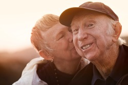Happy man kissed by wife outside during sunset