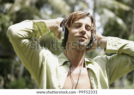 Happy man listening to music with headphones in a tropical garden.