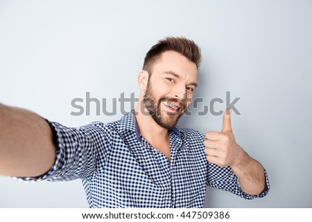 Happy man making selfie and showing thumb up