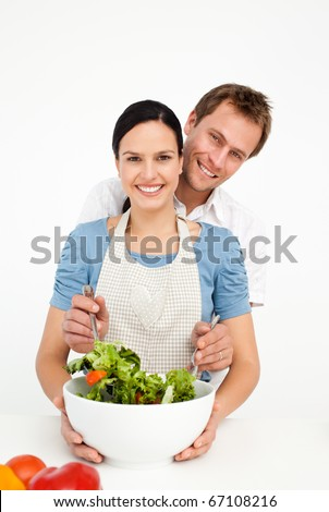 Happy man mixing a salad with his girlfriend in the kitchen at home