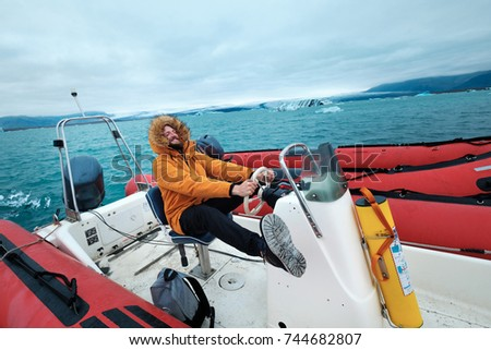 Happy man on a boat on the icy lagoon of Joculsarlon, Iceland #744682807