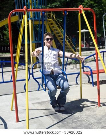 Happy man on child swing.