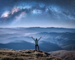Happy man on the mountain peak and arched Milky Way over mountains in low clouds at night. Landscape with blue sky with stars, Milky Way Arch, guy, hills in fog. Space and galaxy. Sky with stars