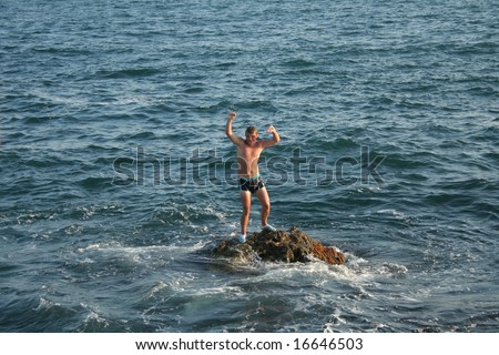 Happy man on the stone in the sea