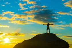 Happy man on top of a mountain with his arms raised against the dramatic sky in the sunset. High achievement, success, winner. Business concept idea. copy space