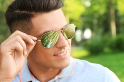 Happy man on vacation. Tropical palm with green leaves reflecting in his sunglasses
