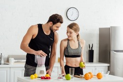 happy man preparing smoothie near sportive girl and fruits