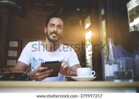 Happy man proprietor of cozy cafe rejoice in own success while sitting with touch pad  at dining table, smiling male holding digital tablet and thinks about something good during lunch in coffee shop