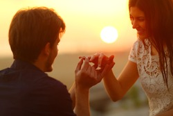 Happy man putting engagement ring in girlfriend finger at sunset on the beach