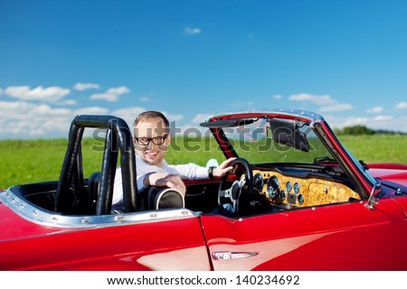 Happy man relaxing in his stylish red cabriolet in lush open countryside looking back at the camera