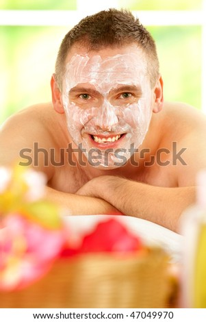 Happy man resting in sunny spa salon laying with facial mask