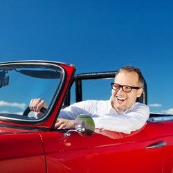 Happy man riding a red convertible car over the bright blue sky