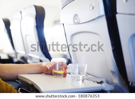 Happy man seating in the aircraft and drinking water before his trip abroad.