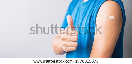 Happy man showing her arm with bandage after receiving vaccine. Vaccination, immunization, inoculation and Coronavirus ( Covid-19 ) pandemic