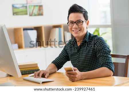 Happy man sitting at his workplace looking at the camera