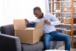 Happy Man Sitting On Sofa Looking Inside Package At Home