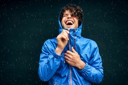Happy man smiling broadly, wearing blue raincoat during the rain outside. Handsome male in blue raincoat enjoying the rain on black wall. Cheerful man has joyful expression in rainy weather.