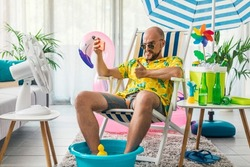 Happy man spending summer vacations at home and pretending he is on a beach, he is sitting on a deckchair and taking selfies with his smartphone