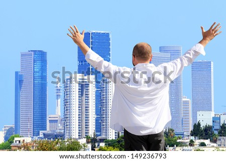 Happy man standing and looking at a cityscape of modern city