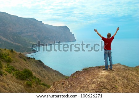 Happy man standing on the cliff with hands up looking at the sea