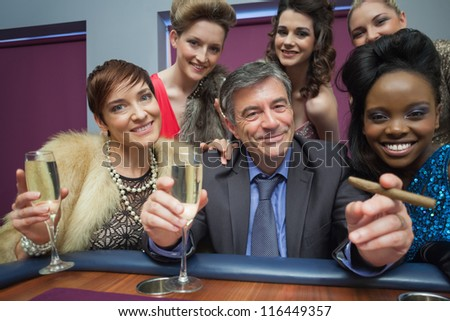 Happy man surrounded by women at roulette table in casino