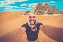 happy man taking crazy selfie with camel in Sahara Desert,  Great Pyramid of Menkaur in the desert of Giza, Egypt