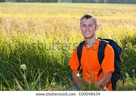 Happy man traveler with a backpack smiling against a background of green nature