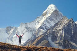 Happy man traveler with backpack hiking in Himalayas with Ama Dablam mountain background.