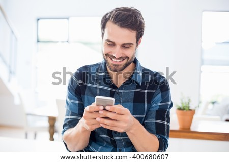Happy man using mobile phone at home