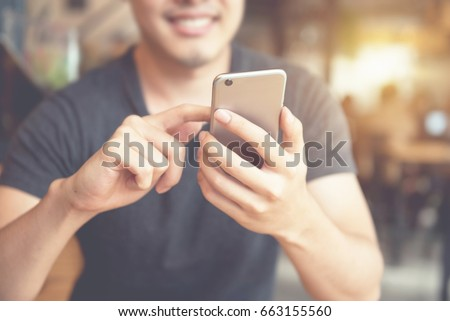 Happy man using smartphone at modern coffee shop, he chatting Online Messaging on mobile phone.