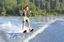 Happy man waterskiing and having fun. Living a healthy lifestyle and staying active. Doing water sports in the summer on a holiday. Copy space