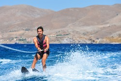 Happy man waterskiing and having fun. Living a healthy lifestyle and staying active. Doing water sports in the summer on a holiday in Greece.
