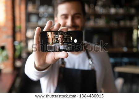 Happy man wearing apron holds smartphone with camera on, waiter or cafe owner make selfie photo focus on device with self portrait image on mobile screen, share life in social media having fun concept